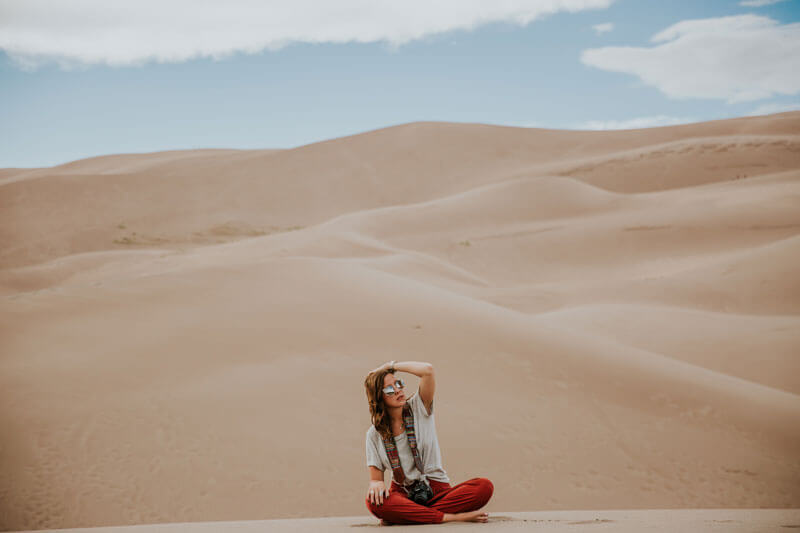 Woman sitting in the desert wearing sun glasses.