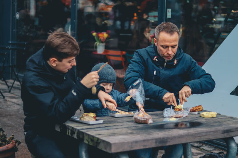 family enjoys meal outside