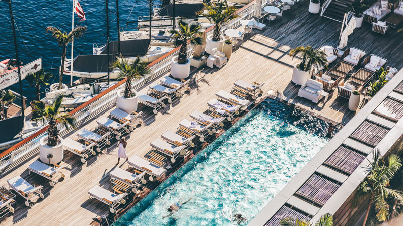 pool on deck by the ocean with deck chairs, palm trees and boats in Monte Carlo, Monaco