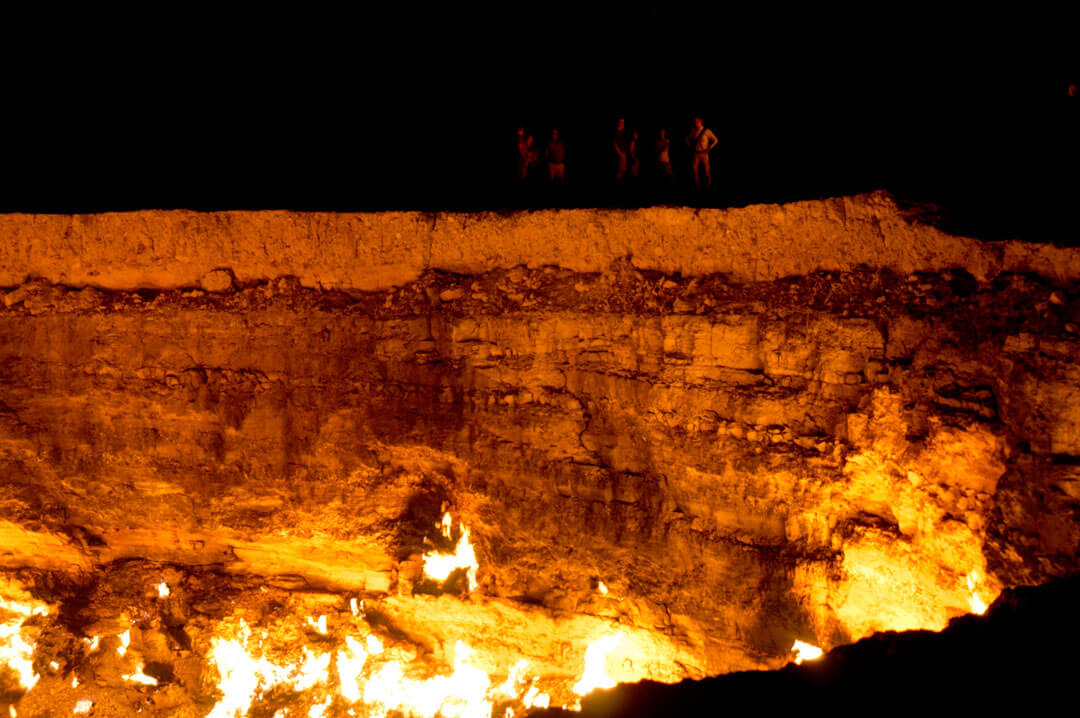 The Darvaza Gas Crater in Turkmenistan at sunrise. Gas coming from the ground is burning in the crater. The diameter of the hole is about 70 m. People can be seen at the edge of the crater illuminated by the light from the fire.