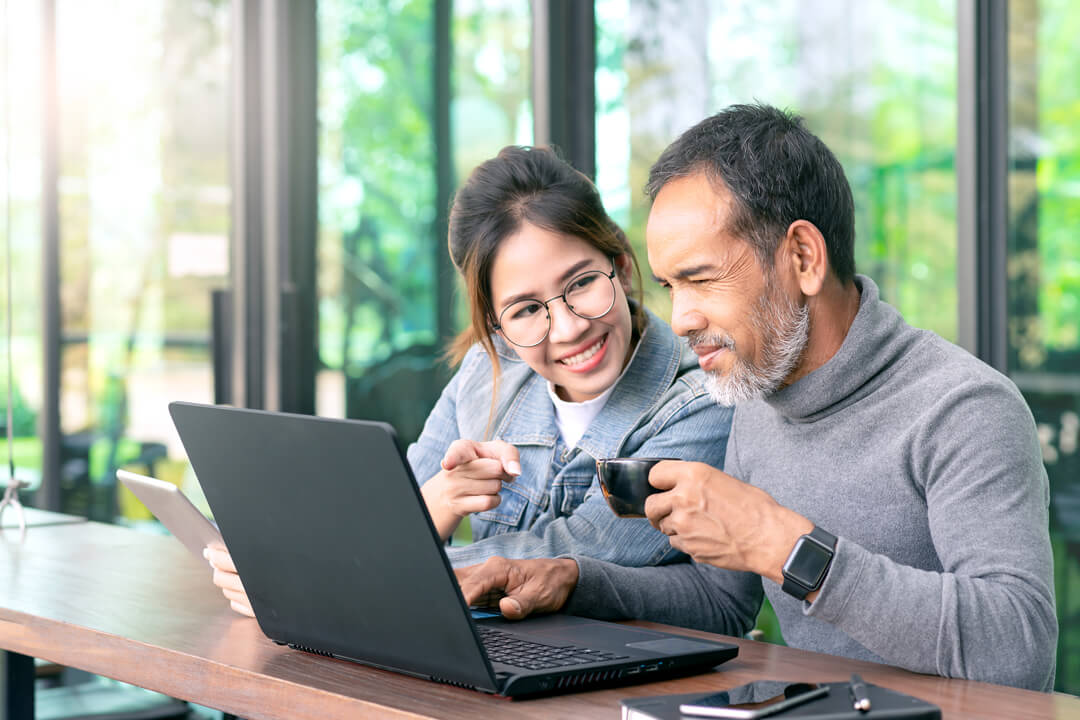 Father and daughter with laptop computer in a cafe