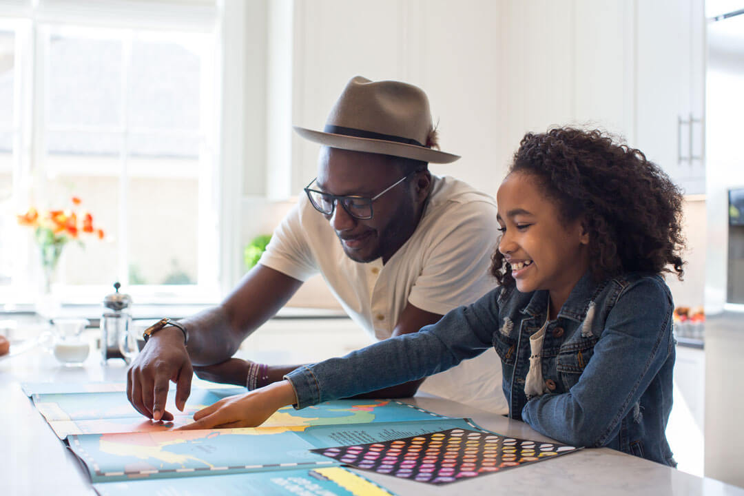 Father and daughter look at map at kitchen counter.