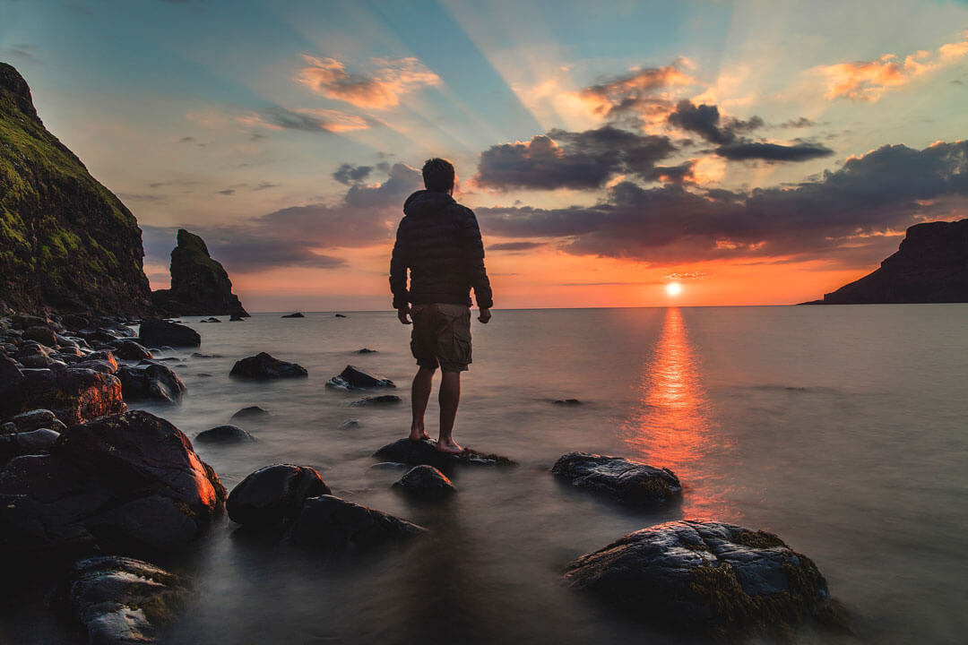 man stands on beach at sunset