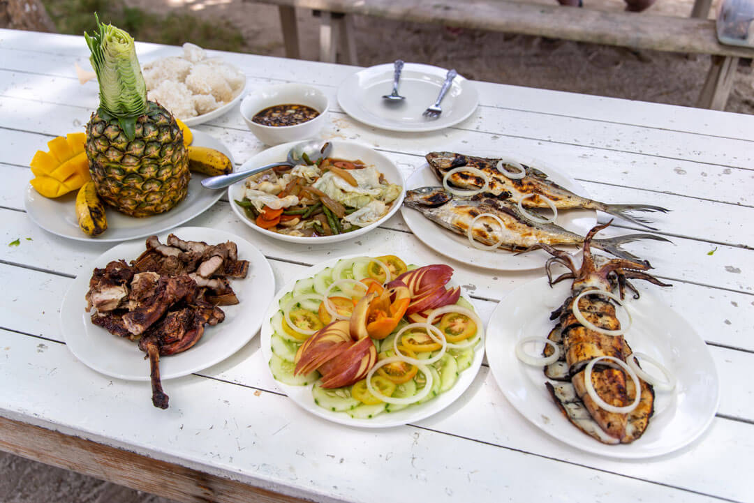Filipino food on a white wood table