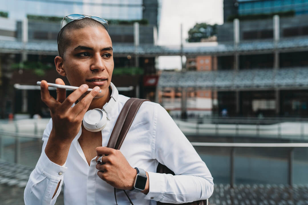 Young adult businessman sending a voicemail with smartphone in the city