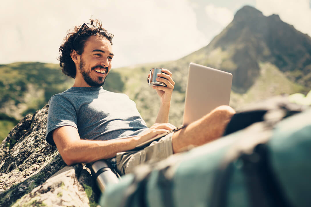 Male hiker having a drink while he's using a laptop on a rock near a lake in the mountain.