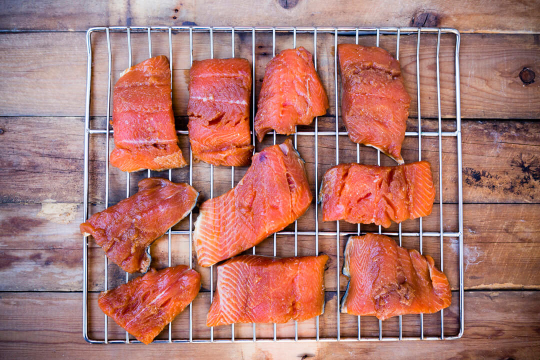 Rack of smoked salmon on rustic wooden background.
