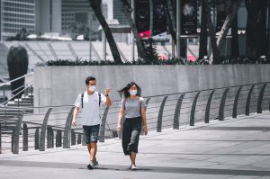 couple walks through empty city with masks on during COVID-19