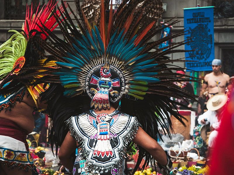 Aztec and Mesoamerican descendants gather at a square in traditional clothing